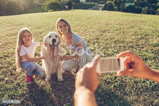 942596618 istock photo Happy family with dog 942596730