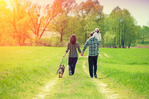 Happy family with dog walking on the rural dirt road