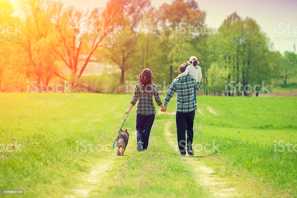 Happy family with dog walking on the rural dirt road stock photo