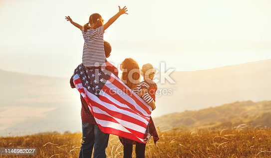 istock happy family with flag of america USA at sunset outdoors 1146982027