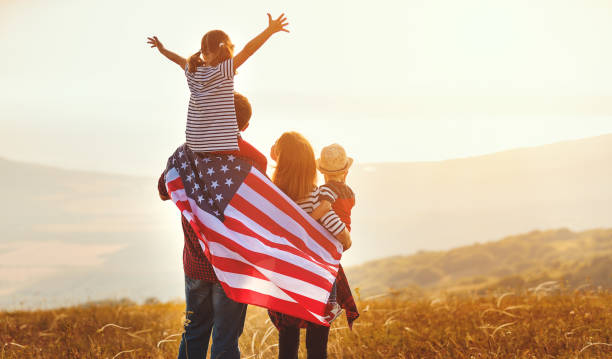 happy family with flag of america usa at sunset outdoors - fourth of july zdjęcia i obrazy z banku zdjęć