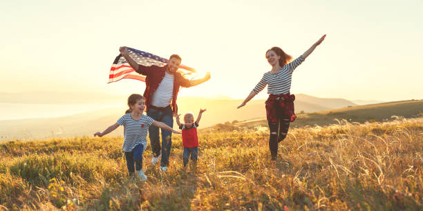 happy family with flag of america usa at sunset outdoors - fourth of july стоковые фото и изображения