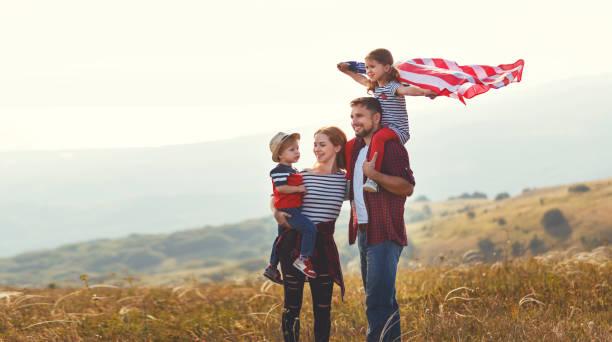 happy family with flag of america usa at sunset outdoors - family 4th of july zdjęcia i obrazy z banku zdjęć