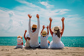 happy family with kids hands up on beach, vacation concept