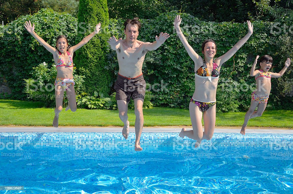 Happy family with kids jumping to swimming pool royalty-free stock photo