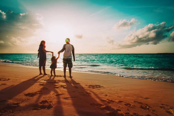 glückliche Familie mit Kindern auf Spiel am Sonnenuntergang Strand – Foto