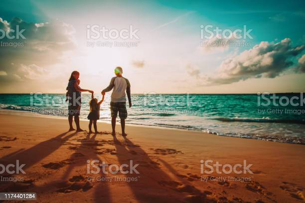 Photo of happy family with kids on play on sunset beach