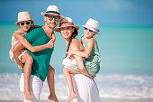Happy beautiful family on white beach walking on the seashore