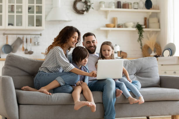 Happy family with kids sit on couch using laptop Happy young family with little kids sit on sofa in kitchen have fun using modern laptop together, smiling parents rest on couch enjoy weekend with small children laugh watch video on computer at home home interior stock pictures, royalty-free photos & images