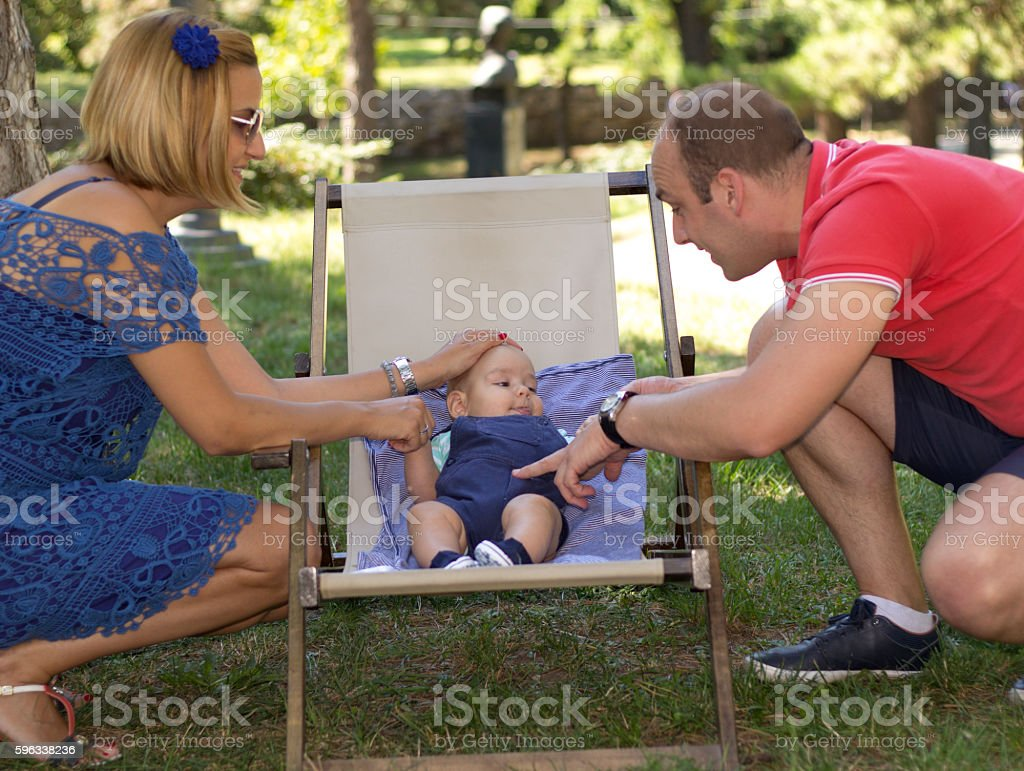 Happy family with little baby sit in textile outdor chair. royalty-free stock photo