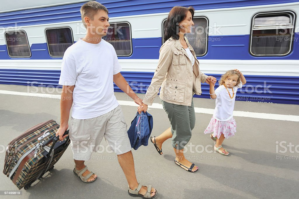 Happy family with little girl going on railway station royalty-free stock photo