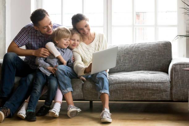 Happy family with little kids enjoying using laptop computer together Happy family with little kids enjoying using application on laptop together, smiling parents spending time with children son and daughter having fun watching video or doing internet shopping at home two parents stock pictures, royalty-free photos & images