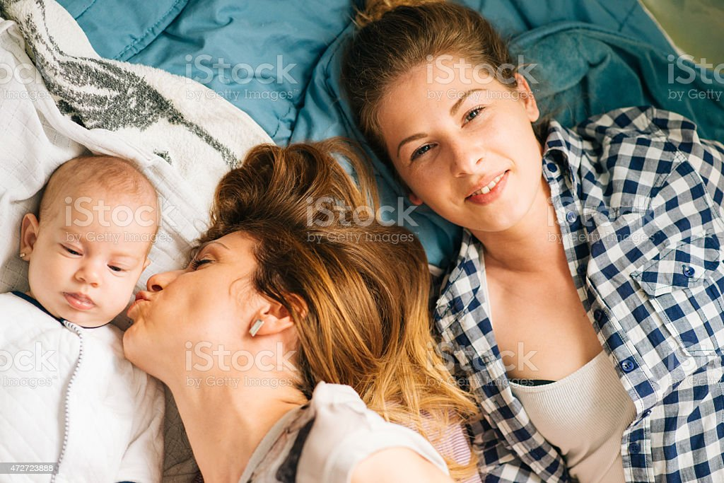 Happy family with mother, baby and aunt lying on bed stock photo