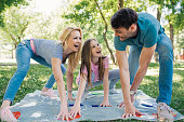 Family playing game at the park with daughter