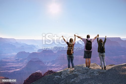 Happy family with raised hands enjoying time together  on top of the  mountain. South Rim, Grand Canyon National Park, Arizona,  USA.