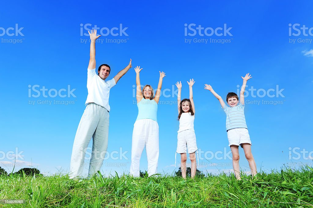 Happy family with raised hands up stands outdoor. royalty-free stock photo