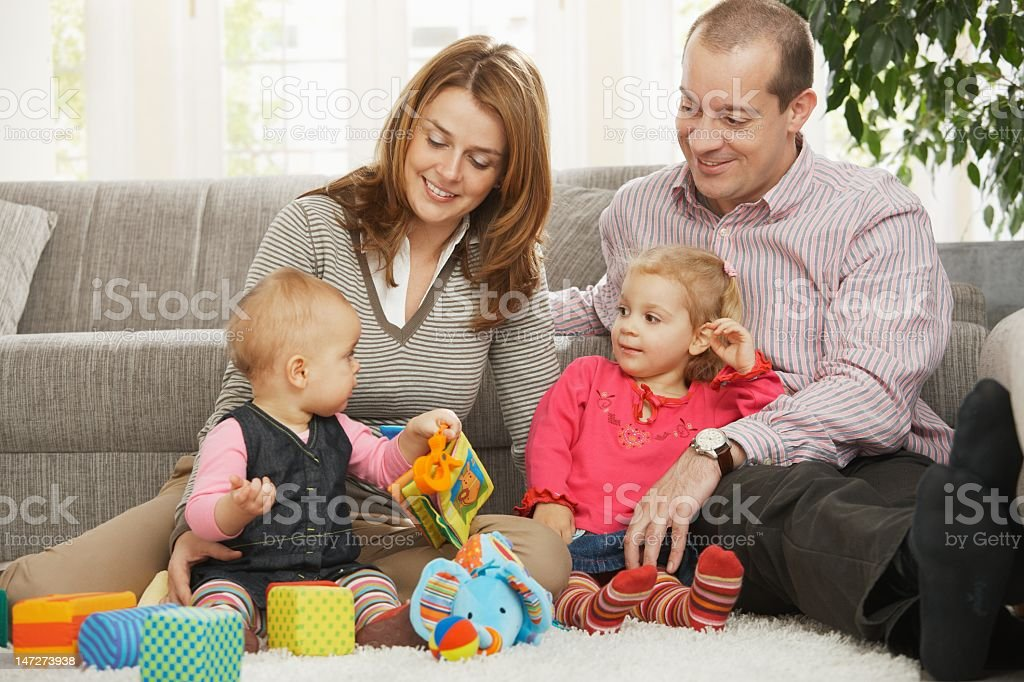 Happy family with toddler and baby playing with toys royalty-free stock photo