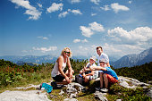 Two brothers and parents were hiking up the mountain on a hot summer day and enjoy a break stop and picnic