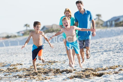 88688880 istock photo Happy family with two boys playing on beach 693374056