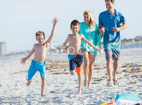88688880 istock photo Happy family with two boys playing on beach 693374114