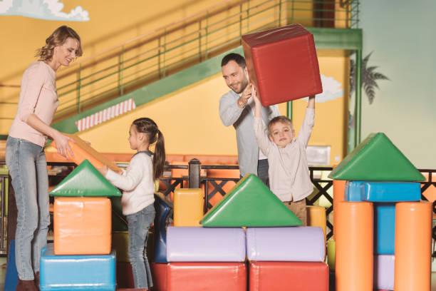 glückliche familie mit zwei kindern schloss mit bunten blöcke in der spielmitte bauen - spielplatz design stock-fotos und bilder