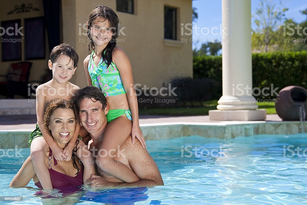 Happy family with two children playing in a swimming pool royalty-free stock photo