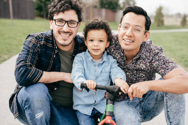 Happy family with two dads and toddler son stock photo