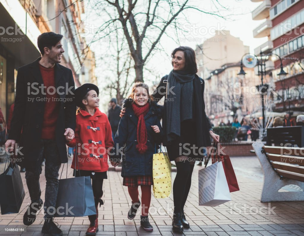 Family with two daughters at shopping during the weekend