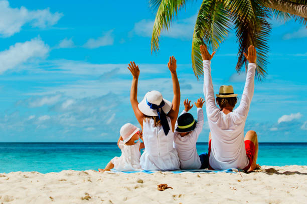 happy family with two kids hands up on beach - family vacation stock photos and pictures