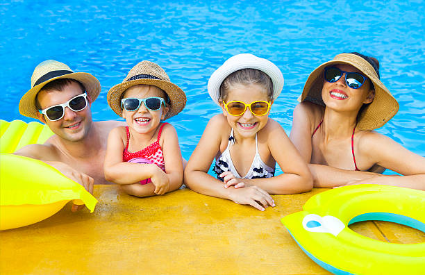 happy family with two kids having fun in swimming pool - standing water stock pictures, royalty-free photos & images