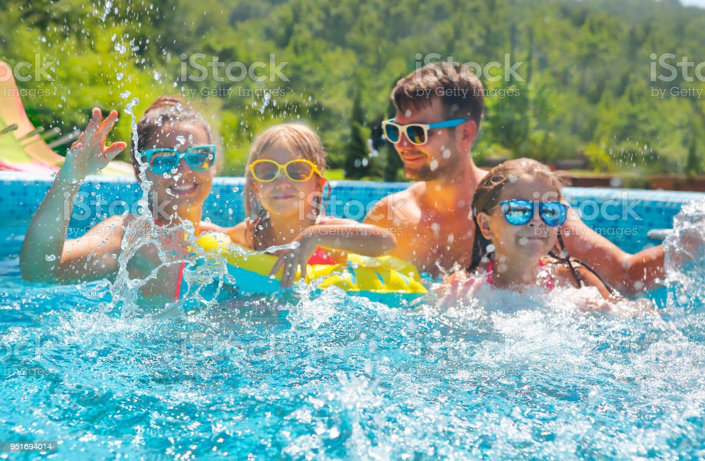 Happy family with two kids having fun in the swimming pool. stock photo