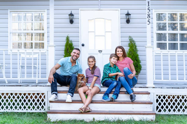 Happy family with two kids sitting in front of american porch stock photo