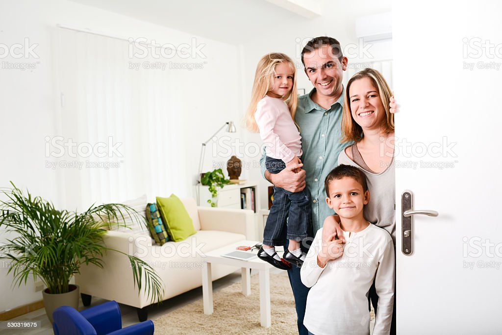 happy family with young kids welcoming guests at the door stock photo