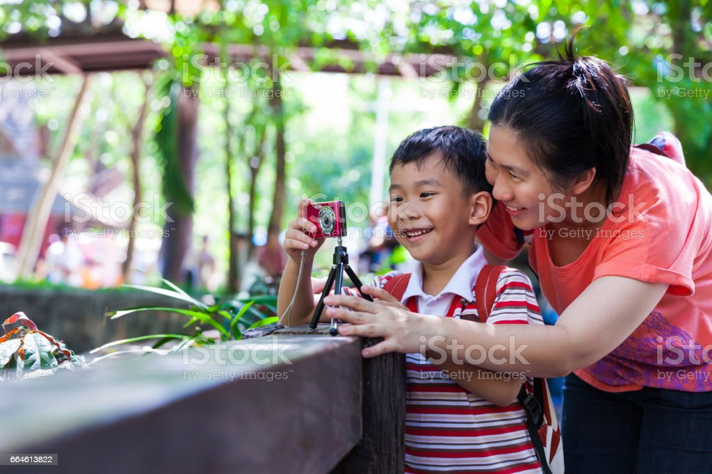 Happy family. Woman teaching boy photographing outdoors. stock photo