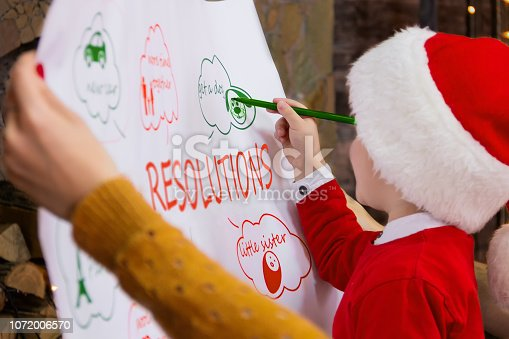 istock Happy Family writing future resolutions in coming 2019 New Year before night of Christmas Eve 1072006570