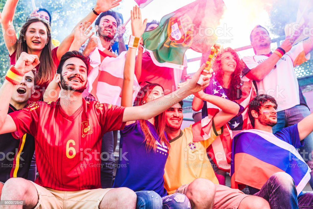 Happy fans supporters at stadium with flags and smoke bomb stock photo
