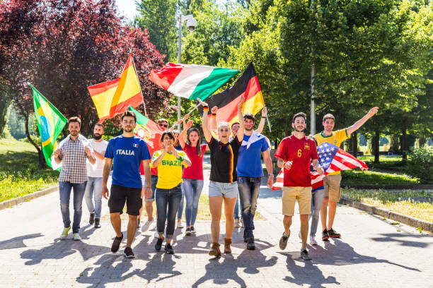 Happy fans supporters from different countries walking and chanting together stock photo