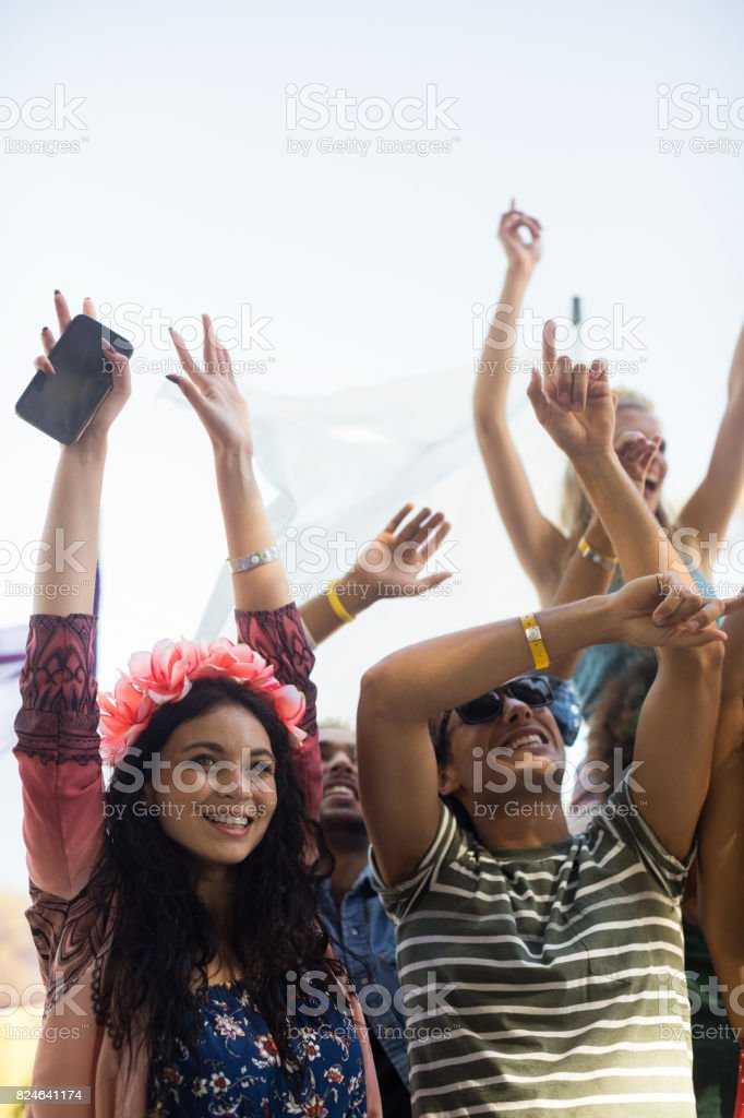 Happy fans with arms raised enjoying at music festival stock photo