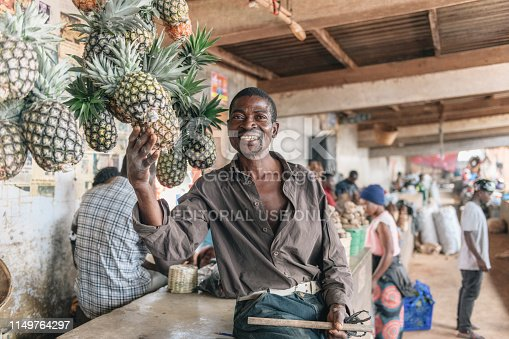 Mzuzu, Malawi - February 27, 2019: market vendor proudly presenting  his pineapple fruits