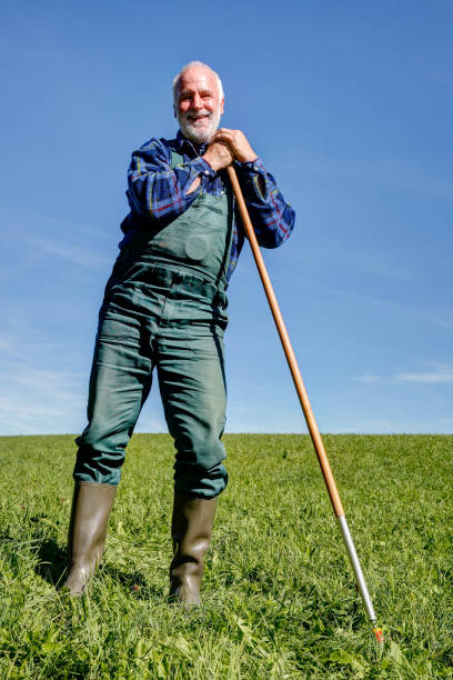 Happy farmer takes a break on his meadow. stock photo