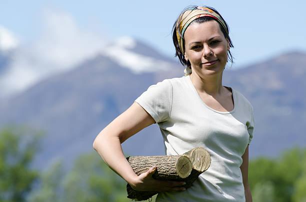 Happy farmer woman with firewood stock photo