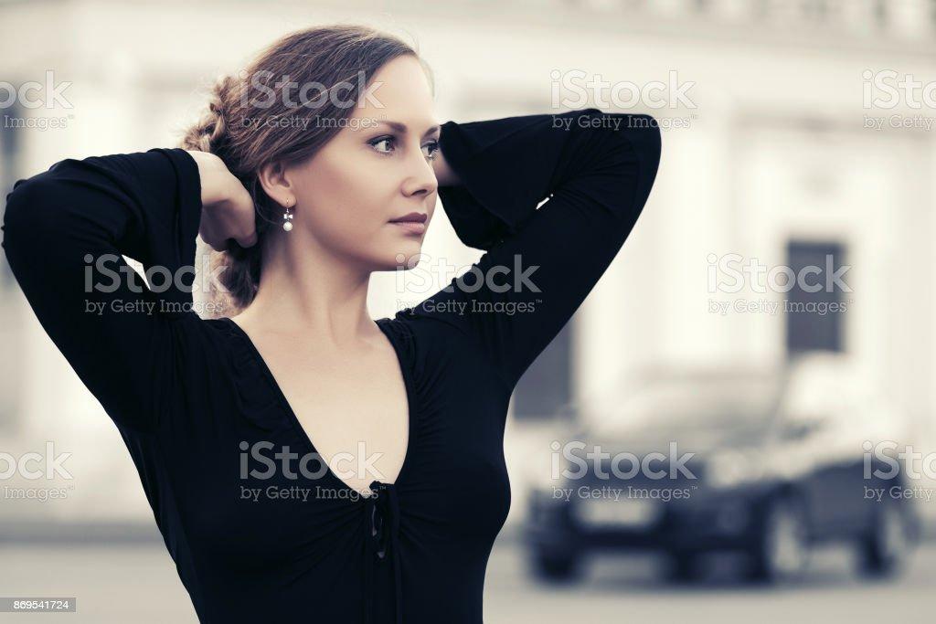 Happy fashion beautiful woman in black blouse walking in city street stock photo
