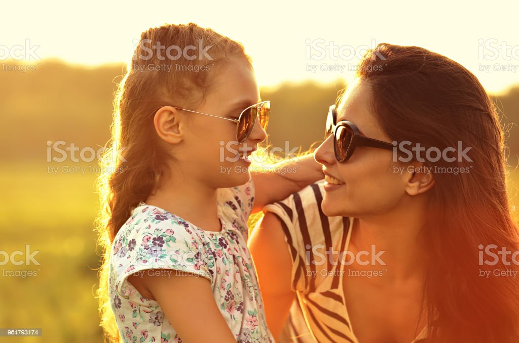 Happy fashion kid girl embracing her mother in trendy sunglasses and looking each other with love on nature background. Closeup portrait. royalty-free stock photo