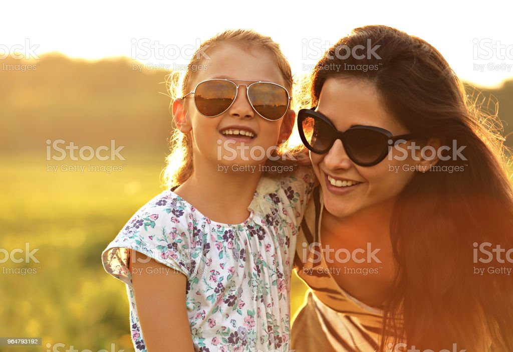 Happy fashion kid girl embracing her mother in trendy sunglasses and looking on nature background. Closeup portrait of happiness. royalty-free stock photo