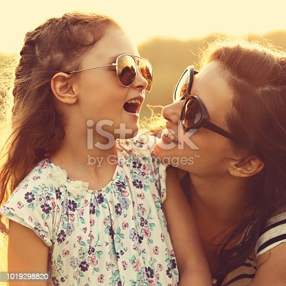 Happy fashion kid girl speaking to her mother in trendy sunglasses on nature sunset background. Closeup portrait of happiness.