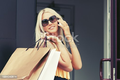 istock Happy fashion woman with shopping bags calling on mobile phone 1004240514