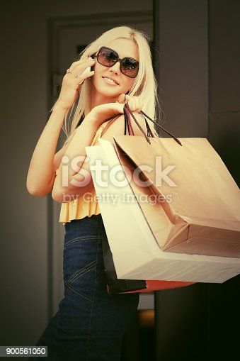 istock Happy fashion woman with shopping bags calling on mobile phone 900561050