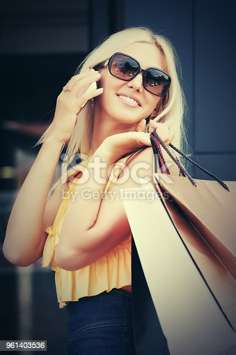 istock Happy fashion woman with shopping bags calling on mobile phone 961403536