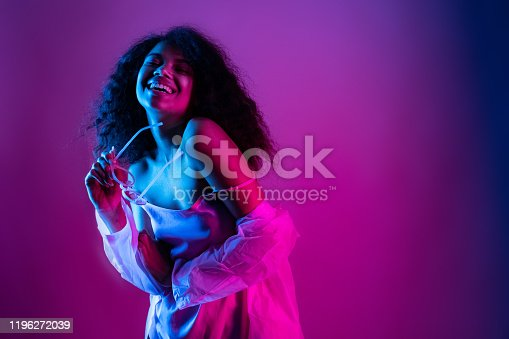Happy beautiful fashion young african american girl hipster black woman hold stylish glasses. wear raincoat look at camera laughing dancing isolated on disco party purple pink trendy studio background