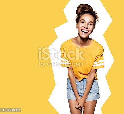 Portrait of young smiling woman wearing bright colourful outfit. Good-looking girl posing indoors. Fashion summer concept. Isolated on white background